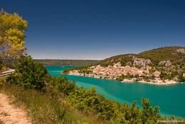 Blick vom gegenüberliegenden Ufer des schmalen südlichen Seitenarms des Lac de Sainte-Croix auf das Dorf Bauduen
