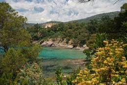 Blick über das azurblaue Wasser des Mittelmeeres zum Empfangsgebäude der Domaine du Rayol