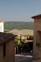 Ausblick zwischen den Häusern hindurch ins Tal mit dem Segelflugplatz von Fayence