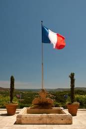 Die Französische Flagge weht vor dem Rathaus von Grimaud, im Hintergrund kann man das Mittelmeer erkennen