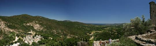 Dies ist ein Teil der Aussicht von der Burg hoch oben in Grimaud, links sieht man die bewaldeten Hänge des Maurenmassivs und die alte Dorfmühle, rechts Teile der Festung und im Hintergrund das Mittelmeer
