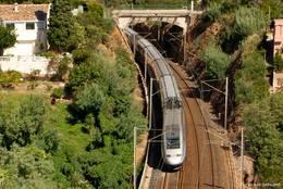 Ein TGV auf der Bahnstrecke entlang der Küste des Esterel-Gebirges bei Le Trayas