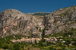 Moustiers-Sainte-Marie am Fuß hoher Felsen im Hintergrund