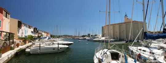 Panorama eines Kanals mit zahlreichen Segelbooten und der Kirche von Port Grimaud im Hintergrund