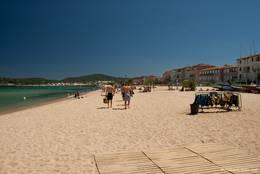 Blick entlang dem feinen Sandstrand von Port Grimaud mit den ersten Ferienhäusern direkt dahinter