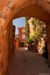 Blick durch einen Torbogen in eine Gasse im Dorf Roussillon