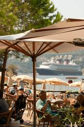 Kleines Strandlokal in Saint-Jean-Cap-Ferrat mit Ausblick auf ein Kreuzfahrtschiff in der Bucht von Villefranche-sur-Mer