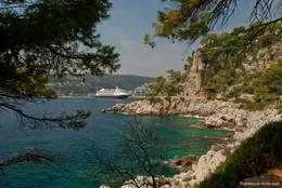 Der Rundweg führt entlang einer steinigen Küstenlinie, im Hintergrund ein Kreuzfahrtschiff
