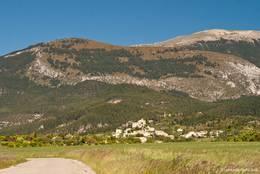 Blick von der Zufahrtsstraße und den Feldern des Plateau de Valensole auf das Dorf Saint-Jurs mit den sich dahinter erhebenden Bergen des Montdenier Massivs