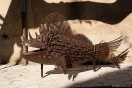 Kunstwerk in Form eines Fisches aus Metall am Straßenrand in Seillans