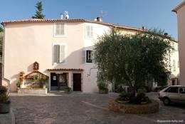 Olivenbaum in den Straßen des Dorfes, links im Hintergrund an der Wand ein mit Blumen verzierter Brunnen