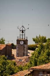 An der Spitze des Turms hängt auch eine Glocke, er wird hier umkreist von zahlreichen Schwalben